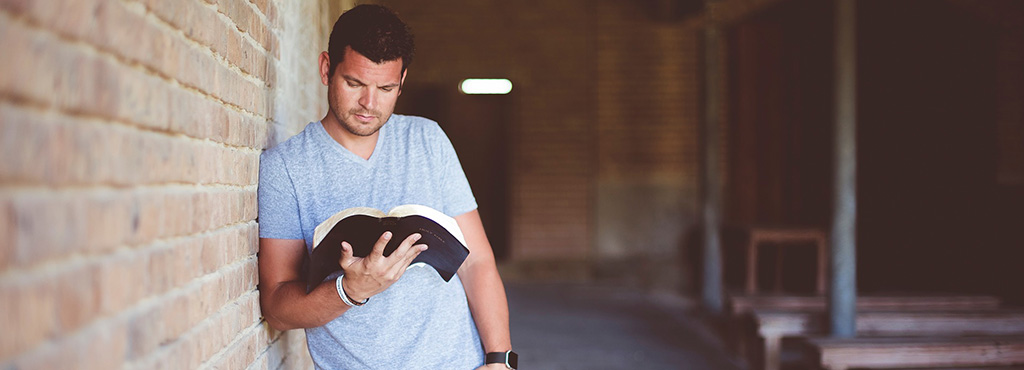 Denver Bible studies - picture of man reading Bible by brick wall